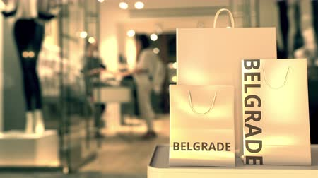 sérvia : Paper shopping bags with Belgrade caption against blurred store entrance. Retail in Serbia related 3D animation