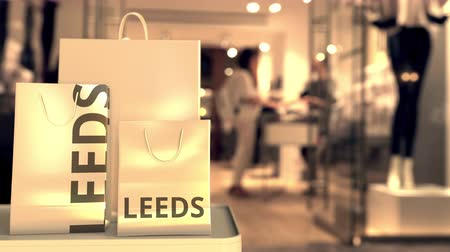 キャプション : Shopping bags with Leeds caption against blurred store entrance. Retail in the United Kingdom related conceptual 3D animation