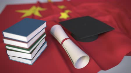 mortarboard : Graduation cap, books and diploma on the Chinese flag. Higher education in China related conceptual 3D animation