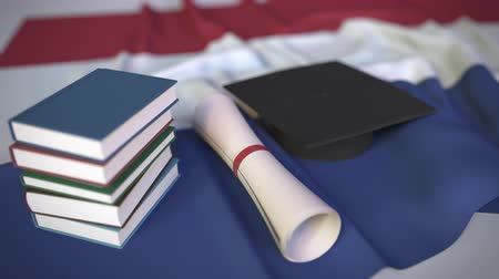 mortarboard : Graduation cap, books and diploma on the Dutch flag. Higher education in the Netherlands related conceptual 3D animation Stock Footage