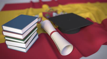 mortarboard : Graduation cap, books and diploma on the Spanish flag. Higher education in Spain related conceptual 3D animation
