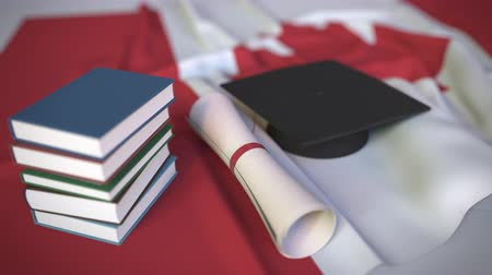mortarboard : Graduation cap, books and diploma on the Canadian flag. Higher education in Canada related conceptual 3D animation