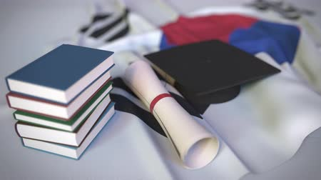 исследование : Graduation cap, books and diploma on the Korean flag. Higher education in South Korea related conceptual 3D animation Стоковые видеозаписи