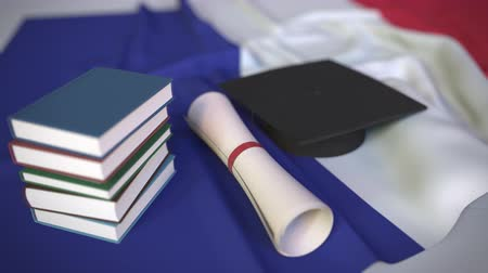 mortarboard : Graduation cap, books and diploma on the French flag. Higher education in France related conceptual 3D animation