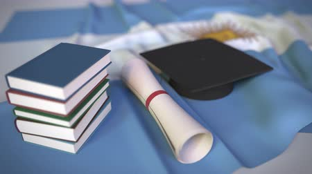 学士 : Graduation cap, books and diploma on the Argentinean flag. Higher education in Argentina related conceptual 3D animation