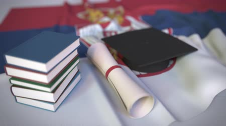 mortarboard : Graduation cap, books and diploma on the Serbian flag. Higher education in Serbia related conceptual 3D animation