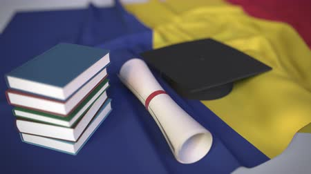 mortarboard : Graduation cap, books and diploma on the Romanian flag. Higher education in Romania related conceptual 3D animation