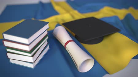 master's degree : Graduation cap, books and diploma on the Swedish flag. Higher education in Sweden related conceptual 3D animation Stock Footage
