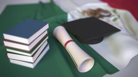 mortarboard : Graduation cap, books and diploma on the Mexican flag. Higher education in Mexico related conceptual 3D animation Stock Footage