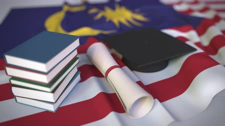 mortarboard : Graduation cap, books and diploma on the Malaysian flag. Higher education in Malaysia related conceptual 3D animation