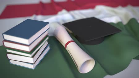 mortarboard : Graduation cap, books and diploma on the Hungarian flag. Higher education in Hungary related conceptual 3D animation