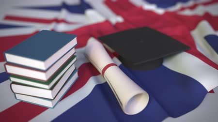 diploma : Graduation cap, books and diploma on the British flag. Higher education in the United Kingdom related conceptual 3D animation