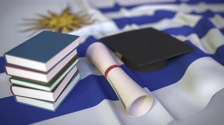 educacion superior : Graduation cap, books and diploma on the Uruguayan flag. Higher education in Uruguay related conceptual 3D animation Archivo de Video