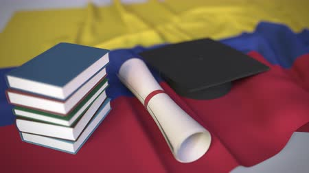 graduação : Graduation cap, books and diploma on the Colombian flag. Higher education in Colombia related conceptual 3D animation