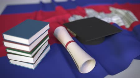 исследование : Graduation cap, books and diploma on the Cambodian flag. Higher education in Cambodia related conceptual 3D animation Стоковые видеозаписи