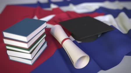 mortarboard : Graduation cap, books and diploma on the Cuban flag. Higher education in Cuba related conceptual 3D animation Stock Footage
