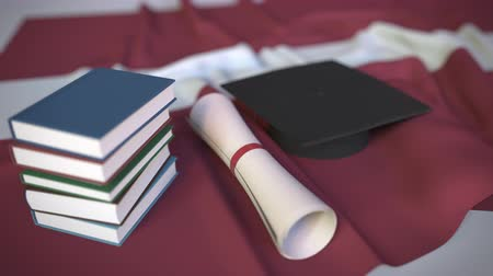Латвия : Graduation cap, books and diploma on the Latvian flag. Higher education in Latvia related conceptual 3D animation Стоковые видеозаписи