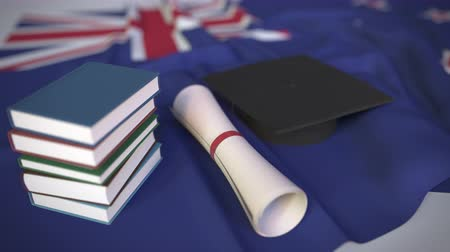 学士 : Graduation cap, books and diploma on the flag. Higher education in New Zealand related conceptual 3D animation 動画素材
