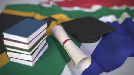 mortarboard : Graduation cap, books and diploma on the flag. Higher education in South Africa related conceptual 3D animation