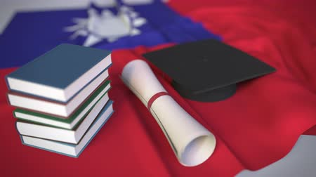 миномет : Graduation cap, books and diploma on the Taiwanese flag. Higher education in Taiwan related conceptual 3D animation Стоковые видеозаписи