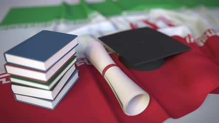 diploma : Graduation cap, books and diploma on the Iranian flag. Higher education in Iran related conceptual 3D animation Stockvideo
