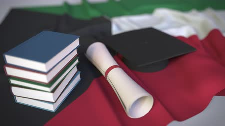 mortarboard : Graduation cap, books and diploma on the Kuwaiti flag. Higher education in Kuwait related conceptual 3D animation