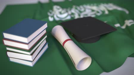 master's degree : Graduation cap, books and diploma on the flag. Higher education in Saudi Arabia related conceptual 3D animation Stock Footage