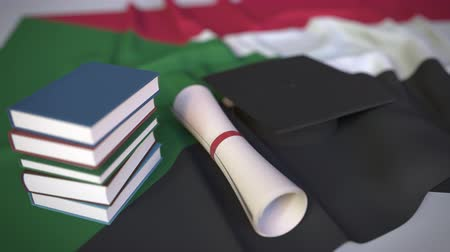 mortarboard : Graduation cap, books and diploma on the Sudanese flag. Higher education in Sudan related conceptual 3D animation