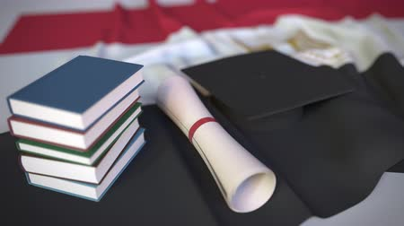 grãos : Graduation cap, books and diploma on the Egyptian flag. Higher education in Egypt related conceptual 3D animation Stock Footage