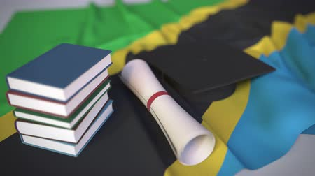 master's degree : Graduation cap, books and diploma on the Tanzanian flag. Higher education in Tanzania related conceptual 3D animation Stock Footage