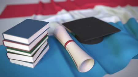 миномет : Graduation cap, books and diploma on the Luxembourgian flag. Higher education in Luxembourg related conceptual 3D animation Стоковые видеозаписи