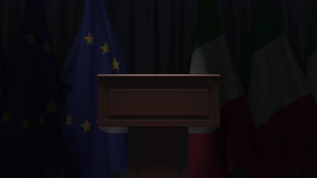 press conference : Flags of the EU and Italy and speaker podium tribune. Political event or negotiations related conceptual 3D animation Stock Footage