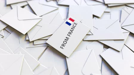 levelezés : Envelope with From France text on pile of other envelopes. International mail related conceptual 3D animation Stock mozgókép
