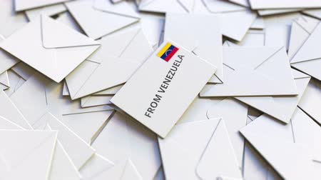 sobre de papel : Envelope with From Venezuela text on pile of other envelopes. International mail related conceptual 3D animation