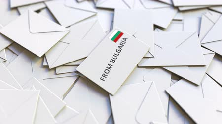 levelezés : Letter with From Bulgaria text on pile of other Letters. International mail related conceptual 3D animation