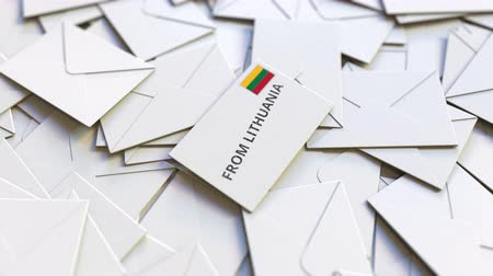 flag of lithuania : Letter with From Lithuania text on pile of other Letters. International mail related conceptual 3D animation