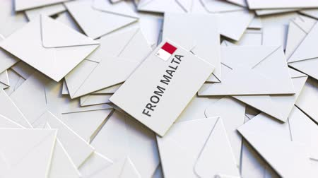 news letter : Letter with From Malta text on pile of other Letters. International mail related conceptual 3D animation Filmati Stock