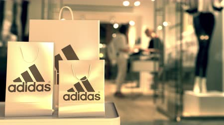 comerciante : Shopping bags with Adidas logo. Editorial shopping related 3D animation