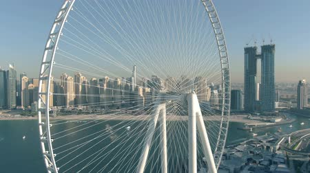 giant wheel : DUBAI, UNITED ARAB EMIRATES - DECEMBER 26, 2019. Aerial shot of the cityscape behind Ain Dubai, the worlds tallest Ferris wheel Stock Footage