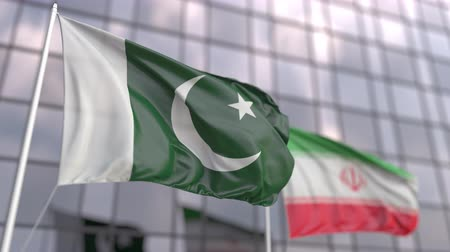 協会 : Waving flags of Pakistan and Iran in front of a modern skyscraper facade