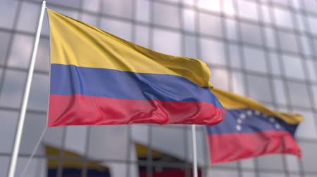 協会 : Waving flags of Colombia and Venezuela in front of a modern skyscraper facade