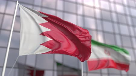 pacte : Waving flags of Bahrain and Iran in front of a modern skyscraper facade