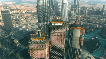 em desenvolvimento : DUBAI, UNITED ARAB EMIRATES - DECEMBER 30, 2019. Aerial view of EMAAR skyscrapers construction site near Burj Khalifa Vídeos
