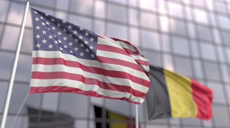 belga : Waving flags of the USA and Belgium in front of a modern skyscraper facade