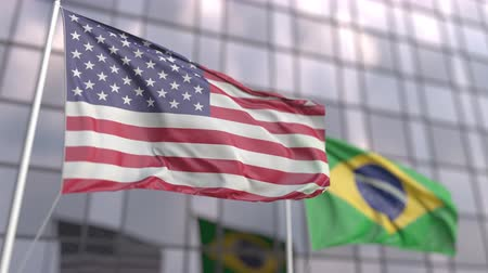 bandiera brasiliana : Waving flags of the United States and Brazil in front of a modern skyscraper facade
