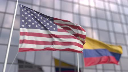 ассоциация : Waving flags of the United States and Colombia in front of a modern skyscraper facade