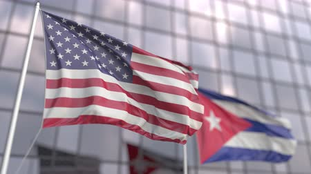 флагшток : Waving flags of the USA and Cuba in front of a modern skyscraper facade