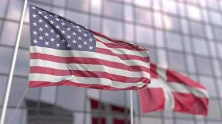 danimarka : Waving flags of the USA and Denmark in front of a modern skyscraper facade