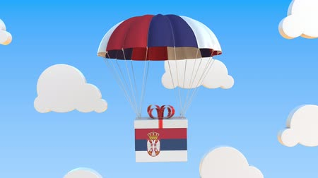 padák : Box with national flag of Serbia falls with a parachute. Loopable conceptual 3D animation