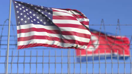 соперничество : Waving flags of the USA and North Korea separated by barbed wire fence. Conflict related loopable conceptual 3D animation Стоковые видеозаписи